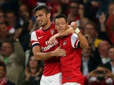 Arsenal's Olivier Giroud celebrates with team mate Mesut Ozil after scoring his team's second goal against Napoli during their Champions League group match on October 1, 2013