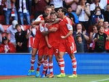 Adam Lallana of Southampton celebrates with team mates as he scores their first goal during the Barclays Premier League match between Southampton and Swansea City at St Mary's Stadium on October 6, 2013