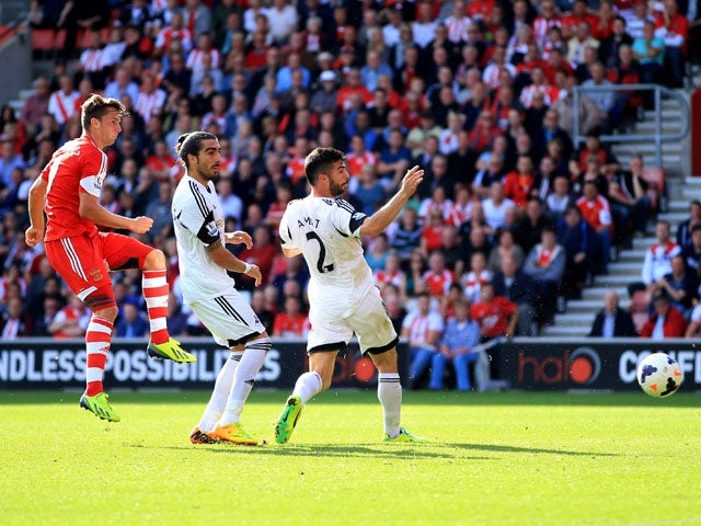 Jay Rodriguez of Southampton shoots past Chico Flores and Jordi Amat of Swansea City to score their second goal during the Barclays Premier League match between Southampton and Swansea City at St Mary's Stadium on October 6, 2013