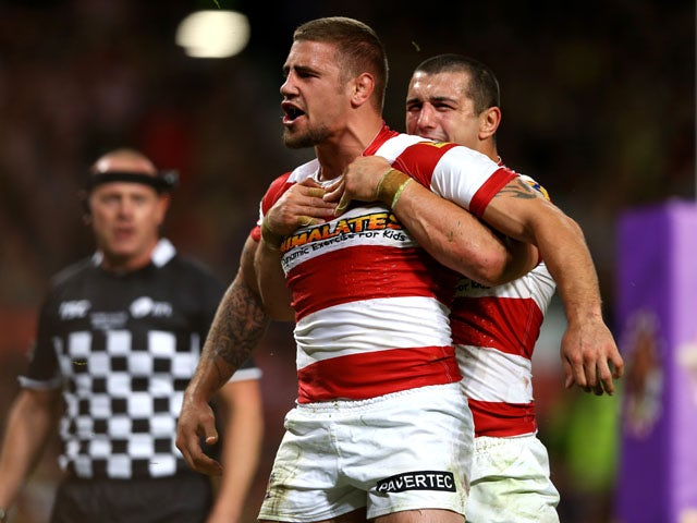 Michael McIlorum of Wigan is hugged by teammate Ben Flower after scoring his team's second try during the Super League Grand Final between Warrington Wolves and Wigan Warriors at Old Trafford on October 5, 2013
