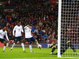 Wayne Rooney of England scores the first goal past Vukasin Poleksic of Montenegro during the FIFA 2014 World Cup Qualifying Group H match between England and Montenegro at Wembley Stadium on October 11, 2013