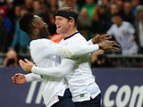Wayne Rooney of England celebrates scoring the first goal with Danny Welbeck of England during the FIFA 2014 World Cup Qualifying Group H match between England and Montenegro at Wembley Stadium on October 11, 2013