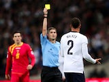 Referee Alberto Undiano Mallenco shows Kyle Walker of England a yellow card during the FIFA 2014 World Cup Qualifying Group H match between England and Montenegro at Wembley Stadium on October 11, 2013
