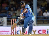 Indian cricket team captain Mahendra Sing Dhoni hits a boundary during the final match of the Tri-Nation series between India and Sri Lanka at the Queen's Park Oval stadium in Port of Spain on July 11, 2013