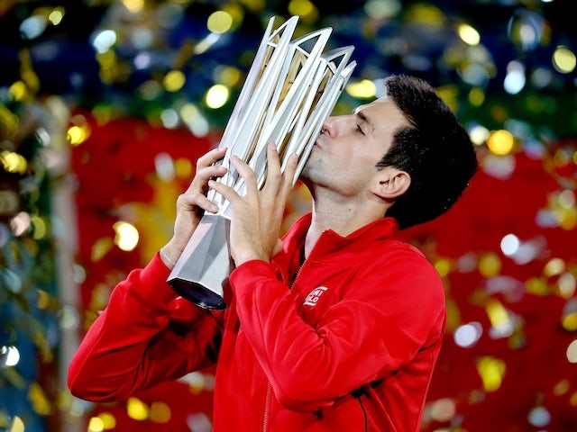 Novak Djokovic of Serbia poses for photographers with the winner's trophy after defeating Juan Martin Del Potro of Argentina in the Shanghai Masters final on October 13, 2013