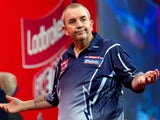 Phil Taylor of Britain reacts as he takes part in the PDC World Championship darts final against Michael van Gerwen of the Netherlands on January 1, 2013