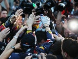 Sebastian Vettel of Germany and Red Bull Racing celebrates with teammates after finishing third to secure his second F1 World Drivers Championship during the Japanese Grand Prix on October 9, 2011