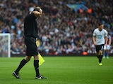 Referee's assistant David Bryan clutches his shirt after he was hit by a missile from the crowd during the Barclays Premier League match between Aston Villa and Tottenham Hotspur at Villa Park on October 20, 2013
