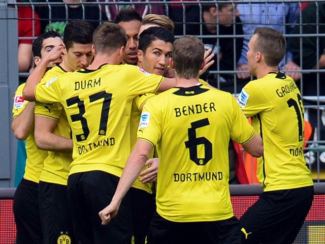 Dortmund's midfielder Nuri Sahin and his teammates celebrate during the German first division Bundesliga football match Borussia Dortmund vs Hannover 96 in the German city of Dortmund on October 19, 2013