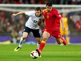 James Milner of England and Fatos Beqiraj of Montenegro compete for the ball during the FIFA 2014 World Cup Qualifying Group H match between England and Montenegro at Wembley Stadium on October 11, 2013