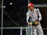 Jenson Button of Great Britain and Brawn GP celebrates on the podium after finishing third during the Abu Dhabi Formula One Grand Prix at the Yas Marina Circuit on November 1, 2009