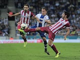 Atletico Madrid's midfielder Juanfran and Atletico Madrid's midfielder Raul Garcia vies with Espanyol's midfielder Abraham Gonzalez Casanovas during the La Liga match on October 19, 2013