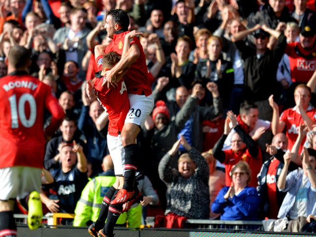 Robin Van Persie #20 of Manchester United celebrates with teammate Michael Carrick after scoring the opening goal during the Barclays Premier League match between Manchester United and Southampton at Old Trafford on October 19, 2013