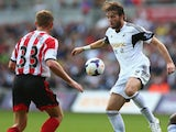 Michu of Swansea City faces upto Lee Cattermole of Sunderland during the Barclays Premier League match between Swansea City and Sunderland on October 19, 2013