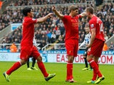 Steven Gerrard of Liverpool celebrates after scoring his 100th Premier League goal and his team's first with team-mates Jordan Henderson and Luis Suarez during the Barclays Premier League match between Newcastle United and Liverpool at St James' Park on O