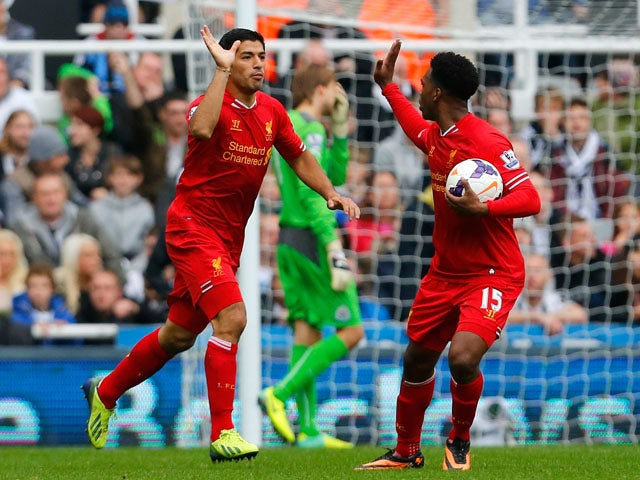 Daniel Sturridge of Liverpool celebrates his team's second goal with team-mate Luis Suarez during the Barclays Premier League match between Newcastle United and Liverpool at St James' Park on October 19, 2013
