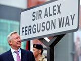 Former Manchester United manager Sir Alex Ferguson unveils a sign after a road near to Old Trafford Stadium was renamed in his honour in Manchester on October 14, 2013