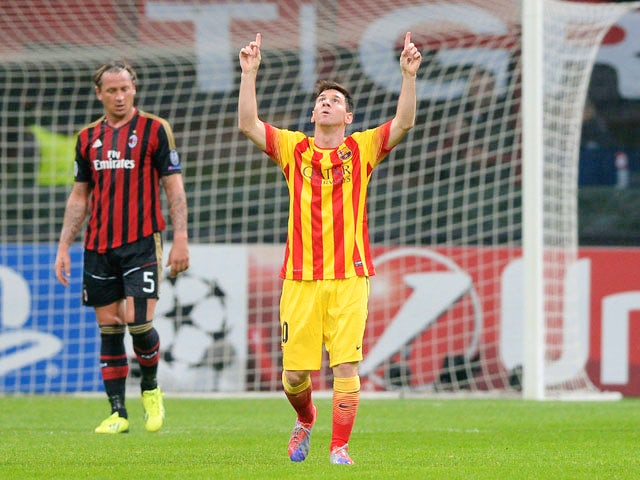 Lionel Messi of FC Barcelona celebrates scoring the first goal during the UEFA Champions League Group H match between AC Milan and Barcelona at Stadio Giuseppe Meazza on October 22, 2013