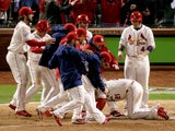 The St. Louis Cardinals surround Allen Craig #21 after he scored the winning run against the Boston Red Sox in the ninth inning during Game Three of the 2013 World Series at Busch Stadium on October 26, 2013