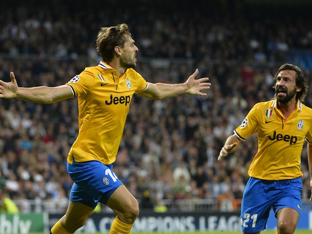 Juventus' Spanish forward Fernando Torres Llorente celebrates with Andrea Pirlo after scoring during the UEFA Champions League Group B football match against Real Madrid on October 23, 2013