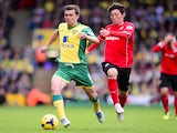Jonny Howson of Norwich City in action with Kim Bo-Kyung of Cardiff City during the Barclays Premier League match between Norwich City v Cardiff City on October 26, 2013