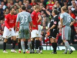 Referee Alan Wiley shows a red card to Nemanja Vidic of Manchester United during the Barclays Premier League match between Manchester United and Liverpool at Old Trafford on March 14, 2009