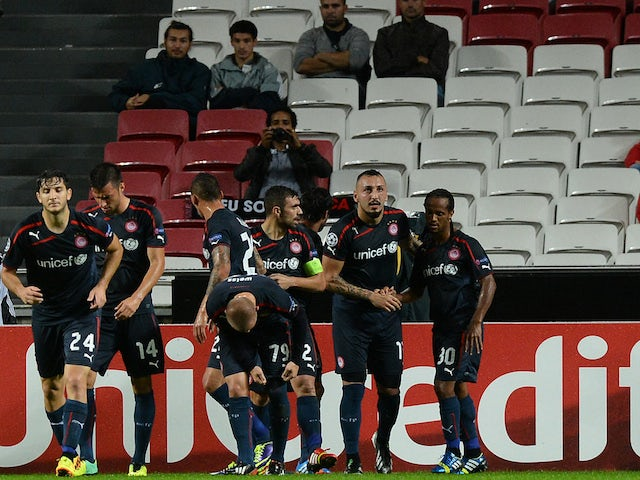 Olympiacos' players celebrate their first goal during the UEFA Champions League group C football match SL Benfica vs Olympiacos FC at Luz Stadium in Lisbon on October 23, 2013