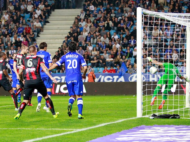 Bastia's French defender Sebastien Squillaci (hidden) scores a goal during the French L1 football match against Nice on October 26, 2013
