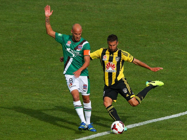 Vince Lia of the Phoenix passes around Ruben Zadkovich of the Jets during the round three A-League match between Wellington Phoenix and the Newcastle Jets at McLean Park on October 27, 2013