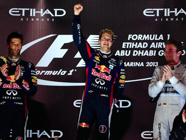Red Bull Racing's drivers German Sebastian Vettel and Australian Mark Webber and Mercedes' German driver Niko Rosberg poses after winning the Abu Dhabi Formula One Grand Prix on November 3, 2013