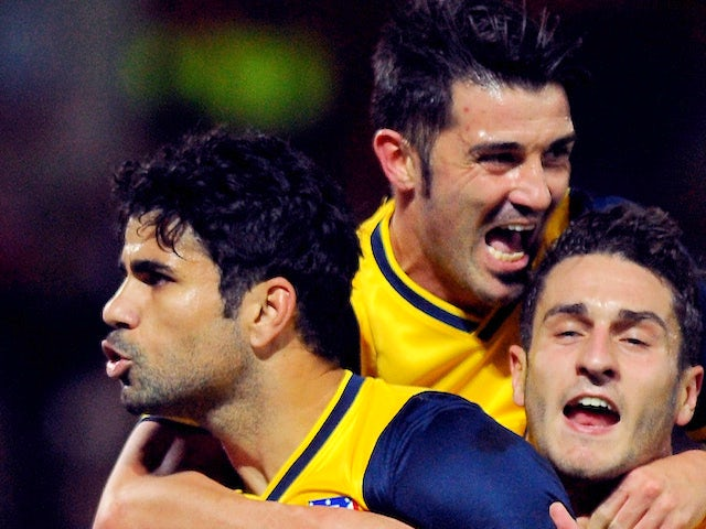 Atletico Madrid's Brazilian forward Diego Costa celebrates with his teammates after scoring on a penalty kick during the Spanish league football match against Granada on October 31, 2013