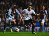 Erik Lamela of Tottenham Hotspur battles with Joe Bennett of Aston Villa during the Capital One Cup third round match between Aston Villa and Tottenham Hotspur at Villa Park on September 24, 2013