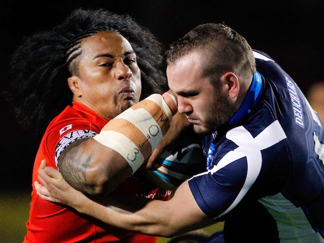 Fuifui Moimoi of Tonga is tackled by Dael Ferguson of Scotland during the Rugby League World Cup Group C match between Tonga and Scotland on October 29, 2013