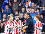 Andrea Dossena of Sunderland is sent off with a red card by referee Andre Marriner as team-mate Sebastian Larsson protests during the Barclays Premier League match between Hull City and Sunderland at KC Stadium on November 2, 2013