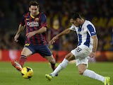 Espanyol's Juan Rafael Fuentes and Barcelona's Lionel Messi battle for the ball on November 1, 2013