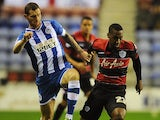 QPR's Junior Hoilett and Wigan's Chris McCann battle for the ball during their Championship match on October 30, 2013