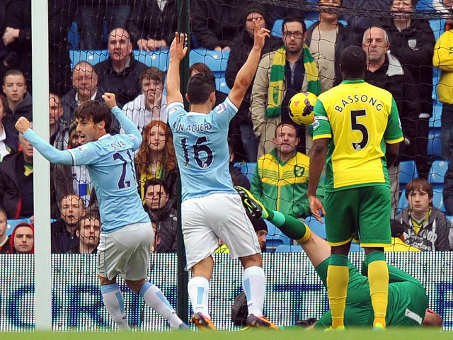 Manchester City's Spanish midfielder David Silva and Manchester City's Argentinian striker Sergio Aguero celebrate their first goal during the English Premier League football match between Manchester City and Norwich City at the Etihad Stadium in Manchest
