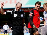 Referee Mike Dean throws down the offending object after being hit by a missile from the crowd during the Coca Cola Championship match between Cardiff City and Swansea on April 5, 2009