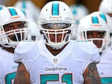 Mike Pouncey of the Miami Dolphins leads the team onto the field during a preseason game against the Jacksonville Jaguars at EverBank Field on August 9, 2013