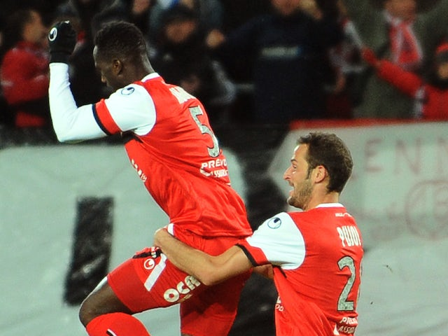 Valenciennes's Benjamin Angoua is congratulated by a teammate after scoring a goal during the French L1 football match against Montpellier on November 9, 2013