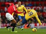 Man United's Chris Smalling and Arsenal's Santi Cazorla battle for the ball on November 10, 2013