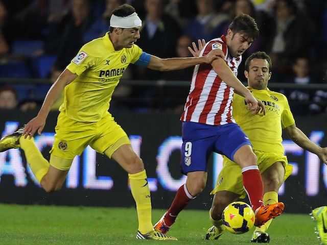 Atletico Madrid's forward David Villa vies with Villarreal pair Bruno Soriano and Jaume Costa during a La Liga game on November 10, 2013
