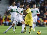 Elche's defender Botia vies with Villarreal's Mexican forward Giovani Dos Santos during the Spanish league football match Elche FC vs Villarreal CF at Martin Valero stadium in Elche on November 4, 2013