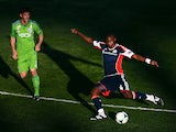 Kalifa Cisse #4 of the New England Revolution kicks the ball under pressure from Brad Evans of the Seattle Sounders during the first half of the FC Tucson Desert Diamond Cup at Kino Sports Complex on February 13, 2013