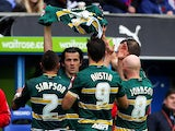 Joey Barton of QPR holds up the shirt of team-mate Alejandro Faurlin as he celebrates with team-mates after scoring the equalising goal during the Sky Bet Championship match between Reading and Queens Park Rangers at Madejski Stadium on November 09, 2013