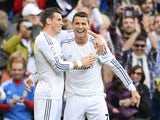 Real Madrid's Portuguese forward Cristiano Ronaldo celebrates with Real Madrid's Welsh striker Gareth Bale after scoring during the Spanish league football match Real Madrid vs Real Sociedad on November 9, 2013