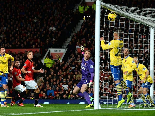 Man United's Robin van Persie heads in the opening goal against Arsenal on November 10, 2013