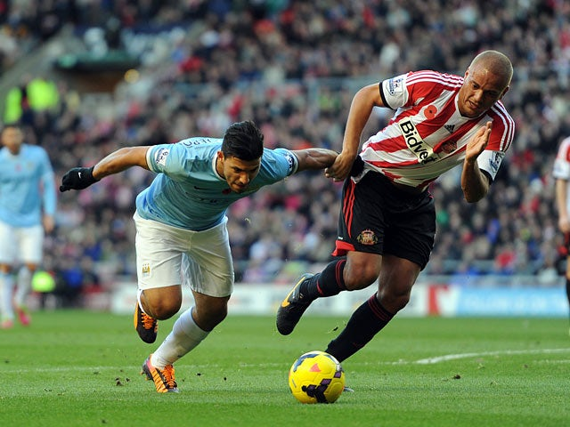 Man City's Sergio Aguero and Sunderland's Wes Brown battle for the ball on November 10, 2013