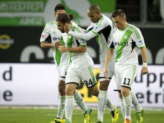 Wolfsburg's Swiss defender Ricardo Rodriguez celebrates scoring his side's first goal with team mates during the German first division Bundesliga football match VfL Wolfsburg vs Borussia Dortmund at the Volkswagen arena in Wolfsburg on November 9, 2013