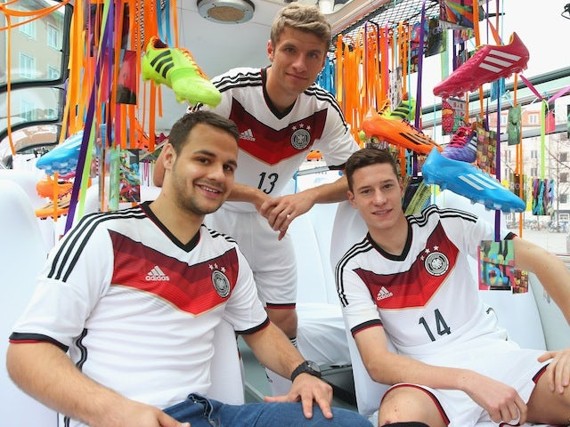 Playmakers Thomas Muller (C) and Julian Draxler (R) help unveil the Germany World Cup kit in Munich on November 12, 2013